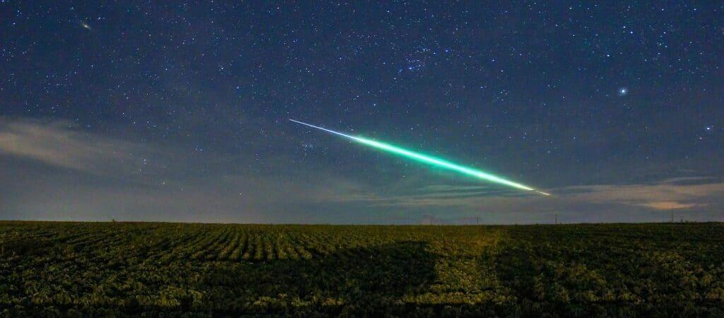 Meteoro de calda azul/verde passando por céu estrelado e campo verde