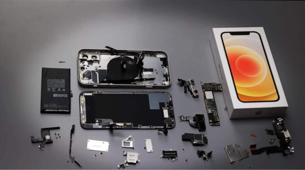 iPhone 12 desmontado, com peças expostas ao lado da caixa do aparelho
