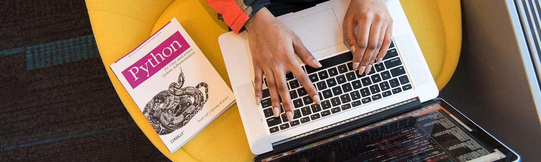 mulher programando em notebook ao lado de livro sobre python