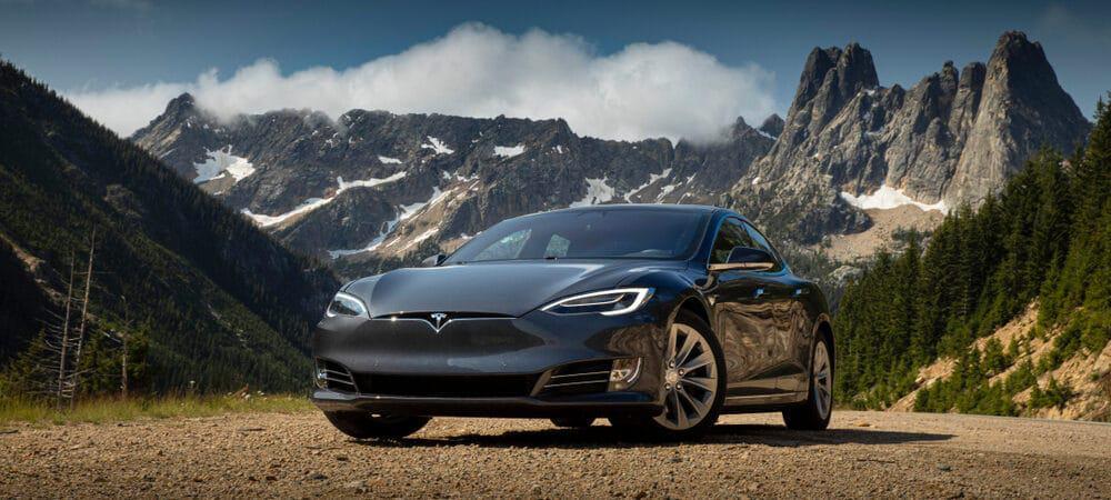 tesla model 3 estacionando diante de montanhas e lago