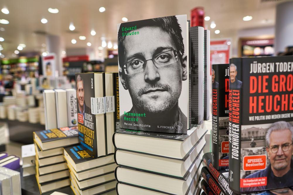 Livros empilhados com foco no livro 'Permanent Record', de Edward Snowden