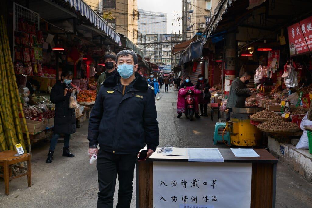 Segurança com máscara facial faz uma triagem de temperatura do lado de fora de um mercado local de frutos do mar, durante o surto do coronavírus na China