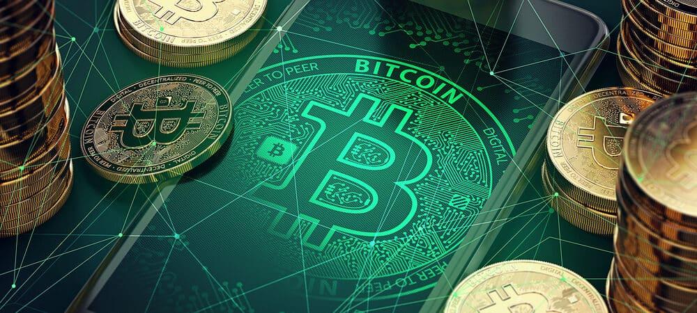 Símbolo bitcoin na tela de um celular e outros bitcoins em moeda ao redor