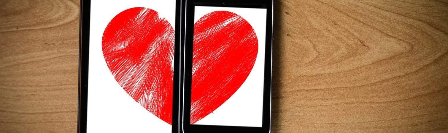 Coração formado por duas metades, cada uma exibida em uma tela de smartphone