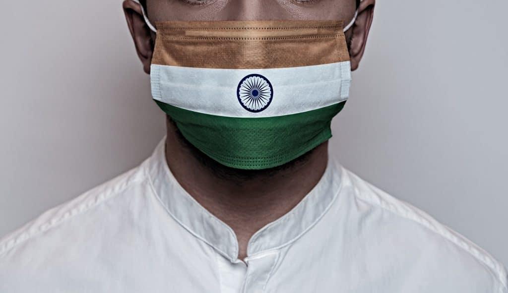 Homem utilizando máscara cirúrgica com estampa da bandeira da Índia