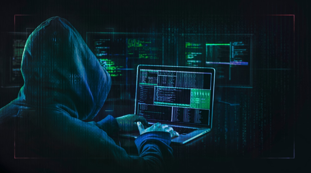Imagem mostra um hacker visualizando dados privados, igual ao que fizeram com o Microsoft Outlook em março de 2021