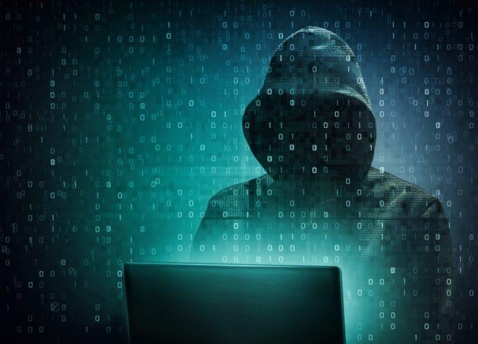 Hacker com capuz em frente ao computador e dados representando informações sobre toda a tela na tonalidade verde