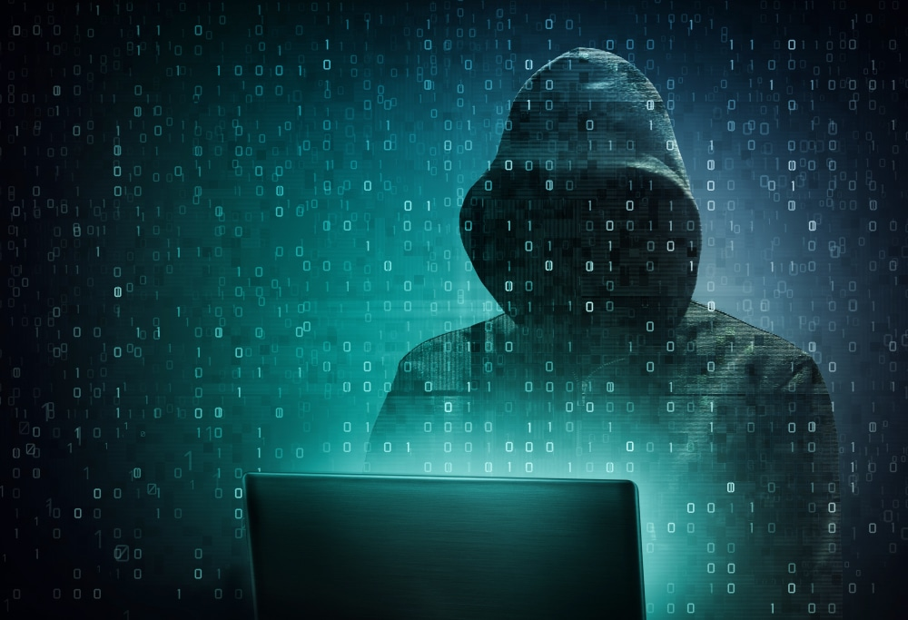 Hacker with hood in front of the computer and data representing information about the entire screen in green tint