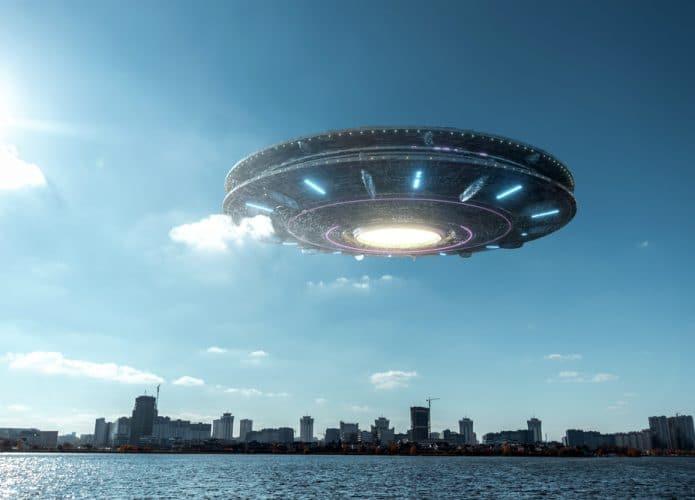 Montagem de uma nave extraterrestre sobre o céu de uma cidade à luz do dia