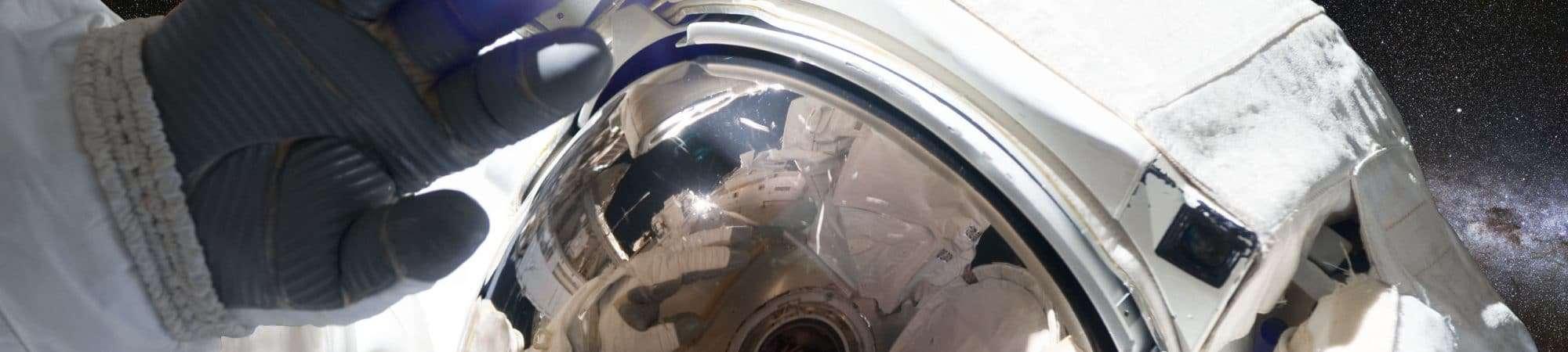Imagem mostra um astronauta, em traje espacial completo, flutuando no espaço e acenando para a câmera