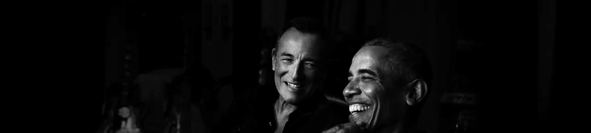 Barack Obama e Bruce Springsteen aparecem sorrindo, em uma foto preto-e-branco com o fundo bem escuro