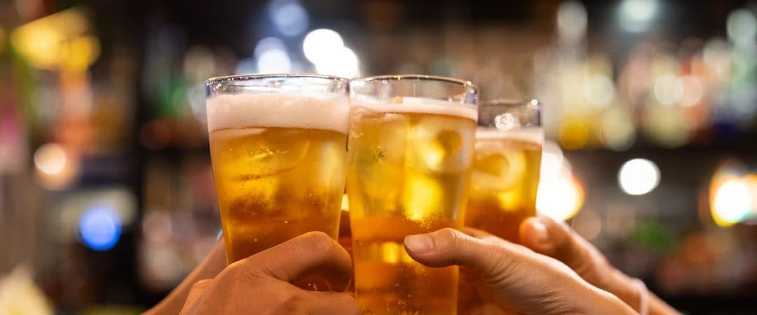 pessoas brindando com copos de cerveja