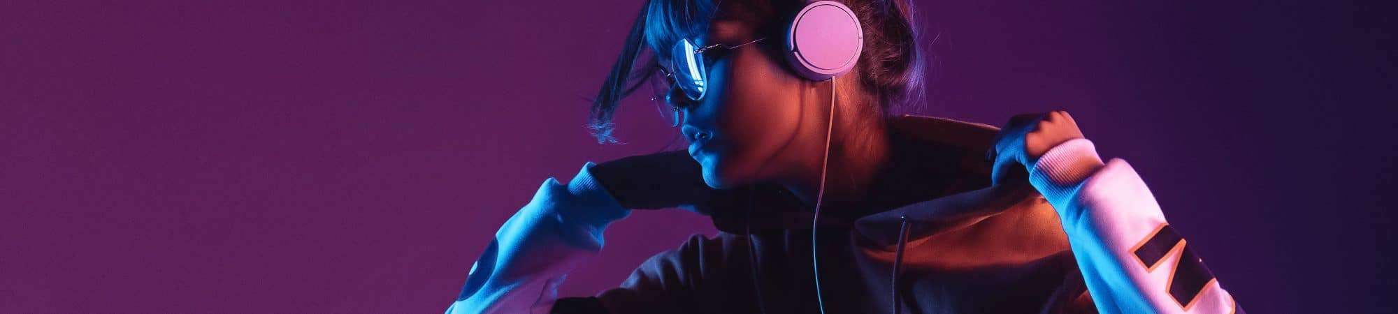 Menina ouvindo música com fone de ouvido em imagem com fundo roxo