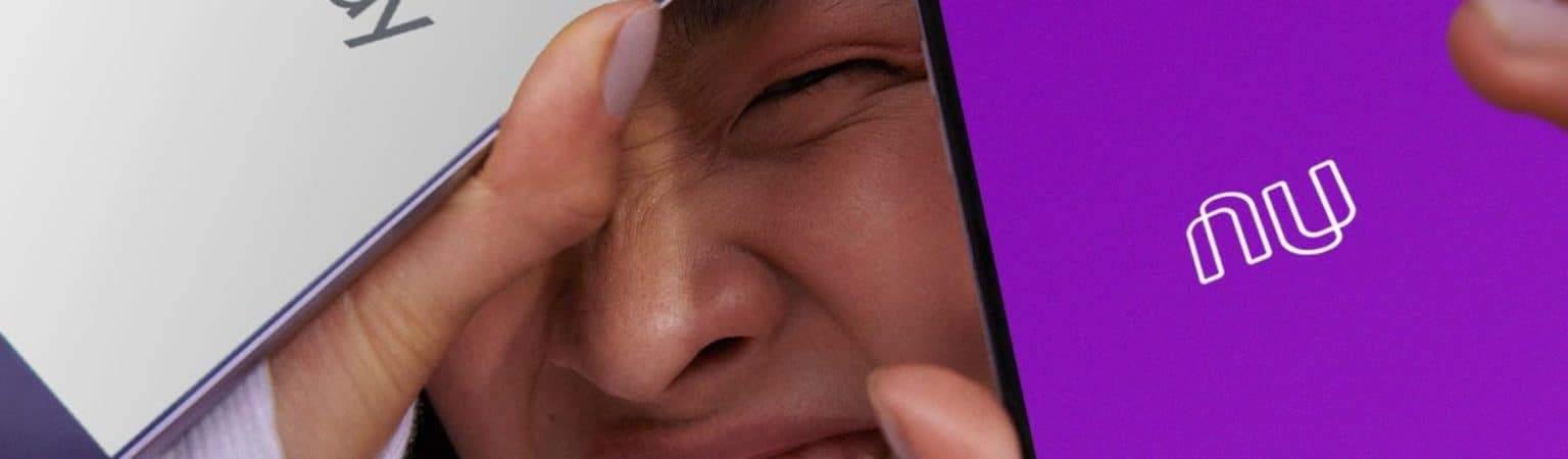 Mulher sorridente mostra dois smartphones com as logos do Nubank e Google Pay