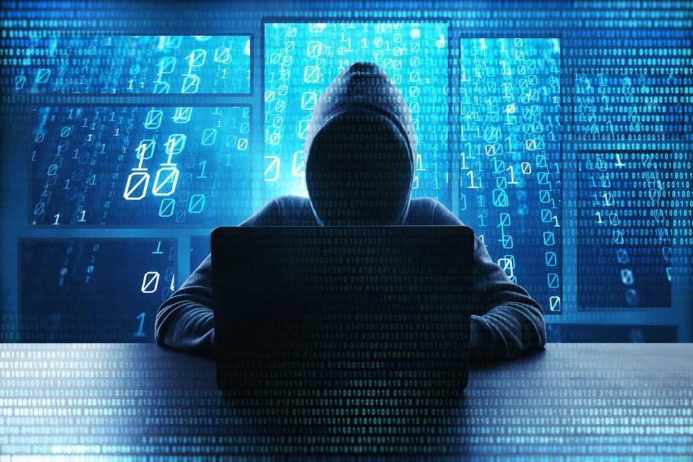Imagem mostrando uma figura encapuzada, simbolizando um hacker nas sombras