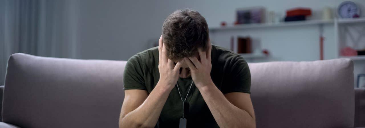 Imagem mostra um soldado sentado em um sofá, com as mãos segurando o rosto em tom de tristeza, simbolizando a depressão