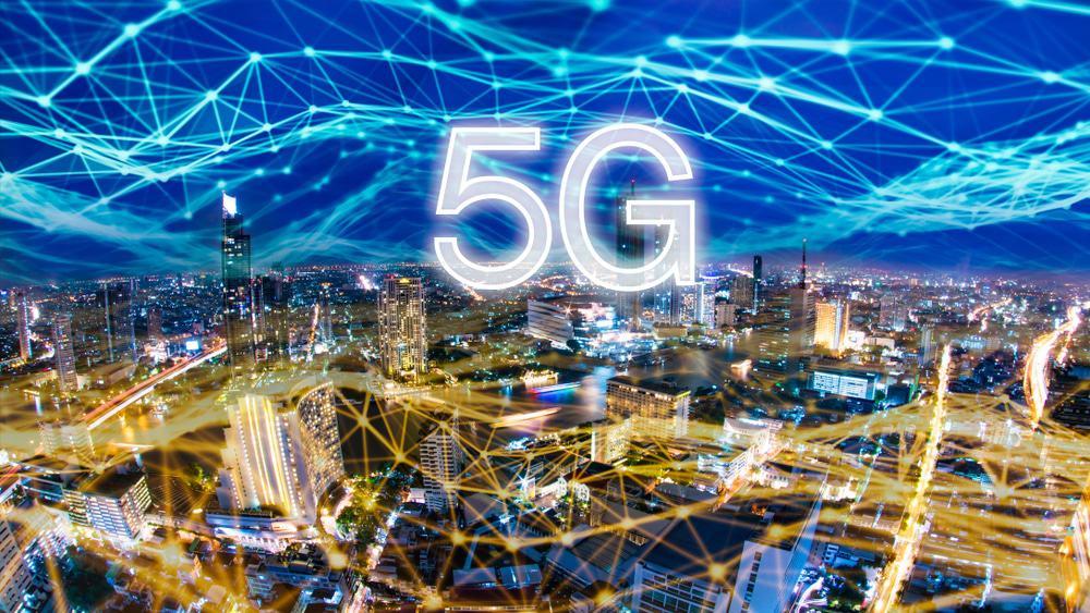 Cidade ilustrada à noite. Por cima há uma rede de luz, como se fosse uma rede de conexão à Iinternet, com o texto 5G por cima.