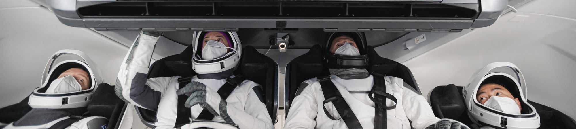 Astronautas da Crew-2, usando trajes espaciais, treinam a bordo de uma cápsula Crew Dragon