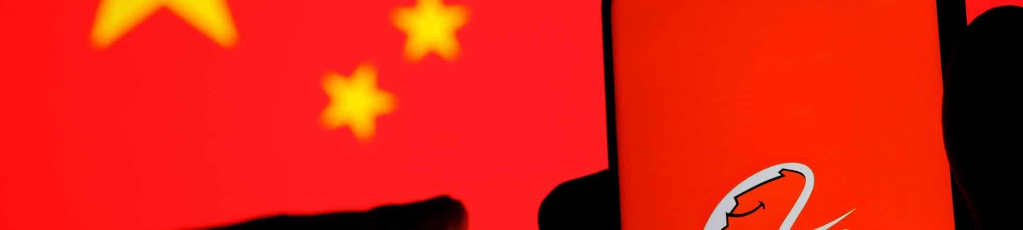 Logo do grupo Alibaba em um smartphone com uma bandeira da China ao fundo
