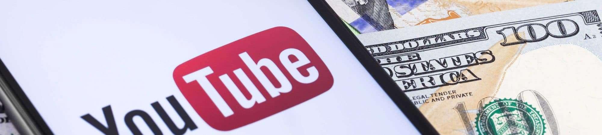 Logo do YouTube sendo exibido em smartphone e notas de dólar ao fundo