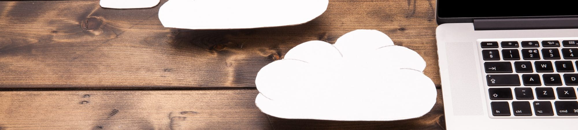 Imagem mostra uma parte de um notebook, em cima de uma superfície de madeira, e ao lado dele algumas nuvens feitas de papel. A ideia é ilustrar a computação em nuvem.