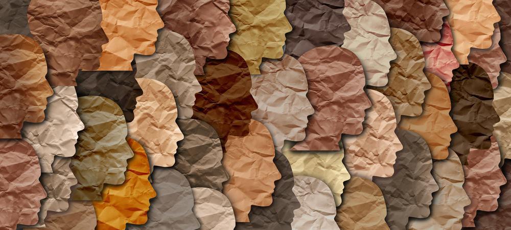 Diversidade ilustrada por papeis recortados em formato de rostos, cada um com uma cor representando diferentes tons de pele