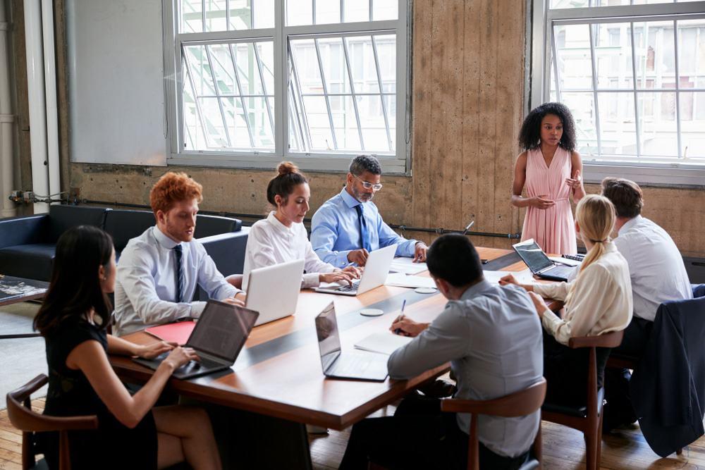 Equipe liderada por uma mulher, em volta de uma mesa de reunião