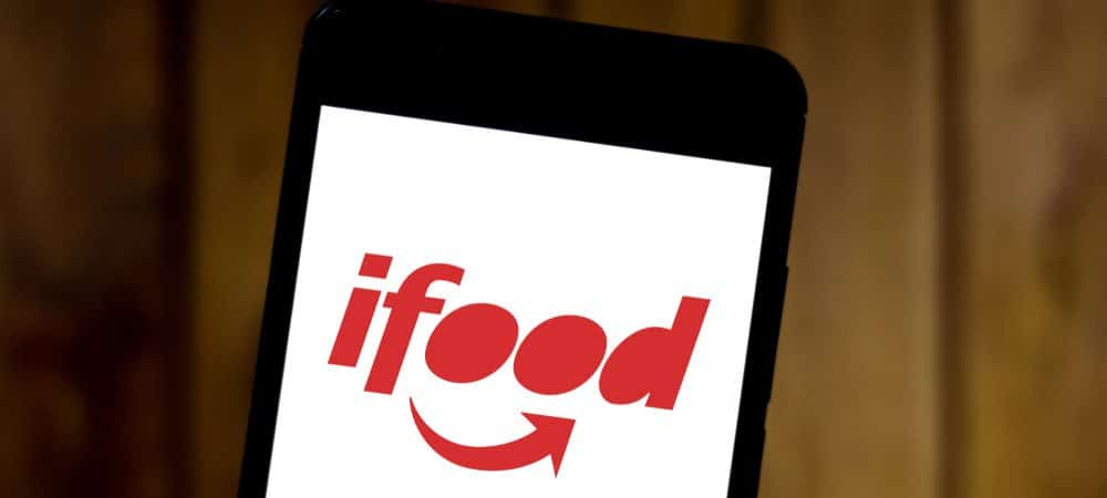 Smartphone mostra logo do iFood na tela. A foto foi tirada em um local com fundo de madeira.