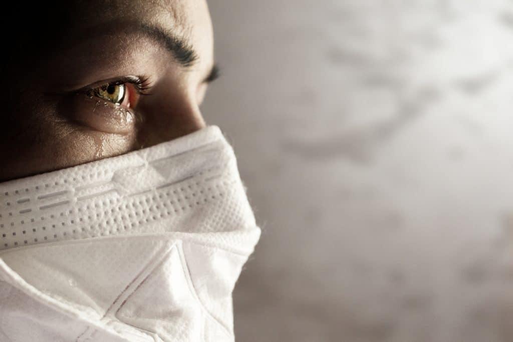 Um ano da primeira morte por Covid-19 no Brasil; Mullher com máscara chora
