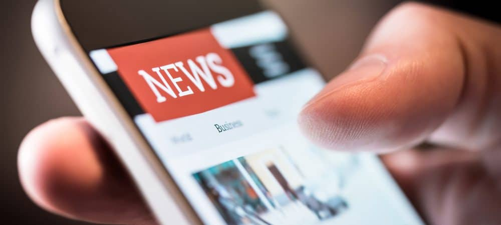 Imagem mostra uma mão segurando um celular e, na tela, aparece a página de um site de notícias