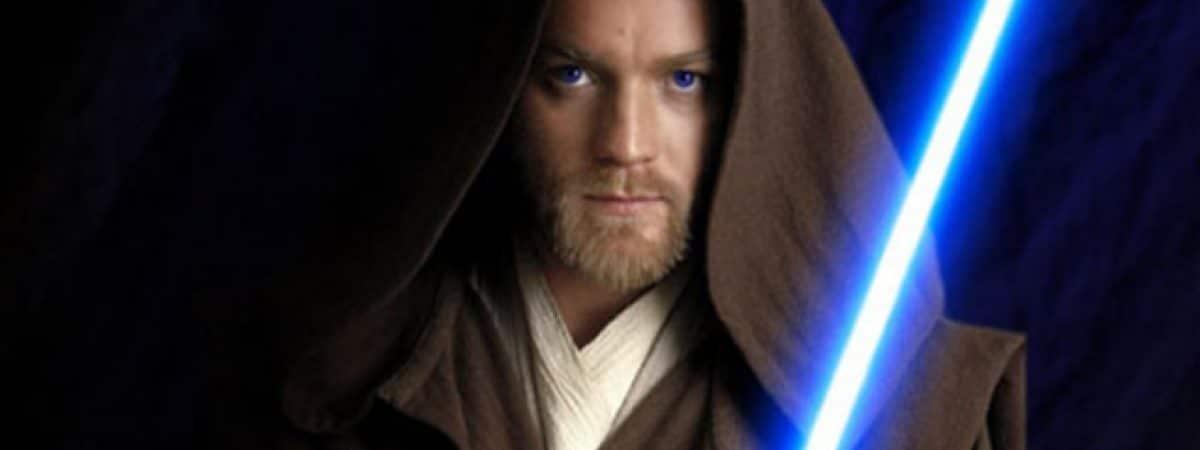 Image mostra Ewan McGregor interpretando Obi-Wan Kenobi: personagem está vestindo um capuz marrom escuro e segurando um sabre de luz de cor azul