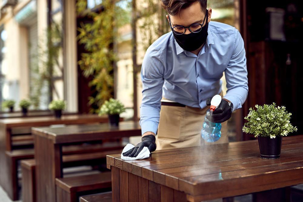 Garçom realiza limpeza das mesas de um restaurante durante a pandemia, utilizando máscara e luvas.