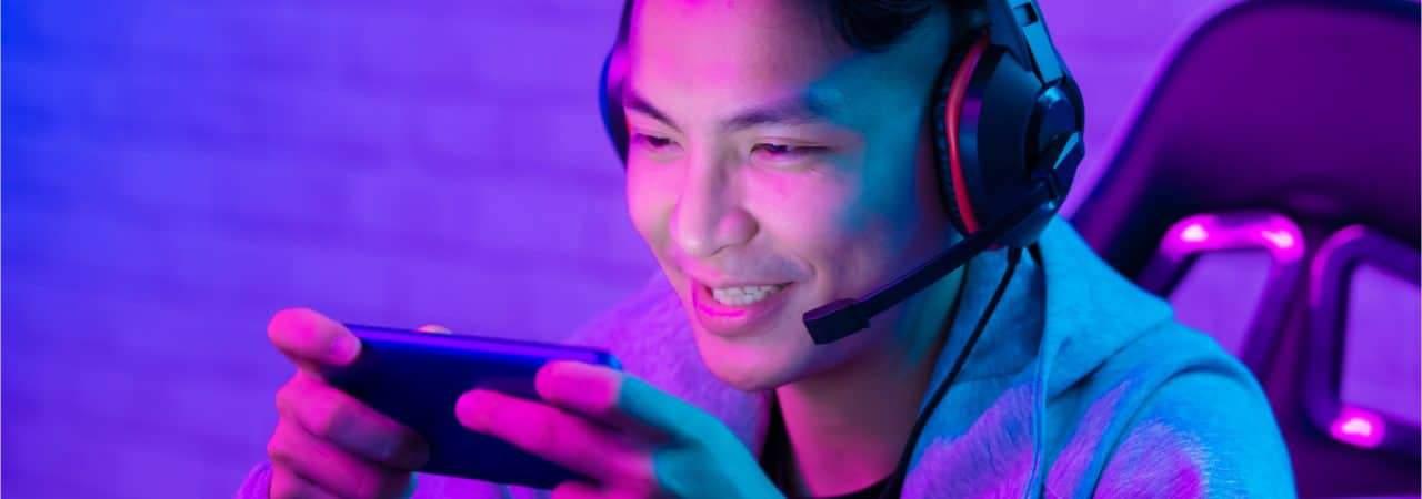 Imagem mostra um jovem sorridente utilizando um headset e jogando em seu smartphone