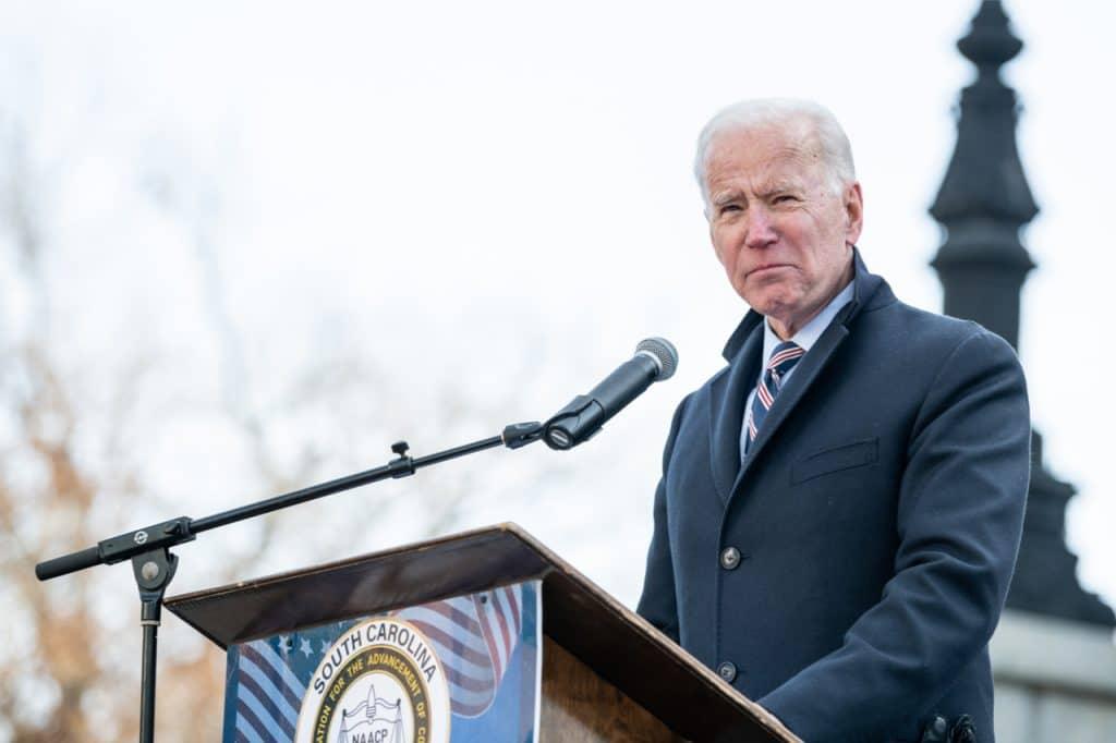 Imagem mostra o presidente americano Joe Biden, falando em um púlpito ao ar livre, em um dia frio