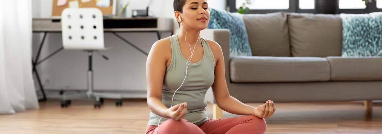 Mulher meditando por meio de um aplicativo de celular