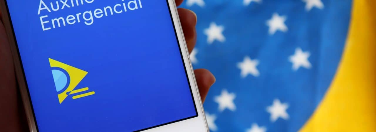 Smartphone exibindo o app do auxílio emergencial com uma bandeira do Brasil ao fundo