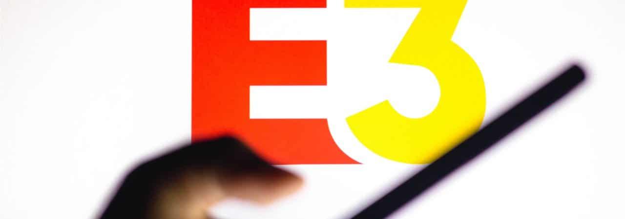 Inagem mostra a logomarca da feira E3 de videogames, com uma mão segurando um celular à frente