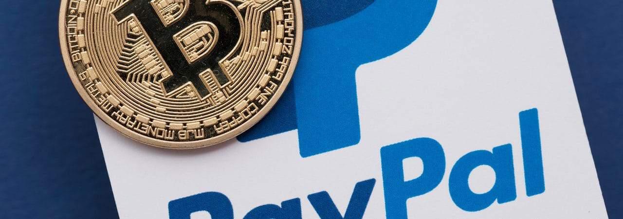 Ilustração de criptomoedas em cima de uma logo do PayPal