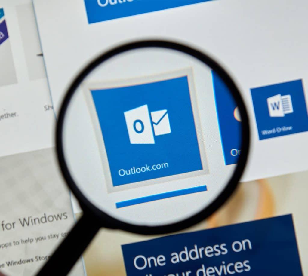 Imagem mostra o ícone do programa Microsoft Outlook, ampliado por uma lupa