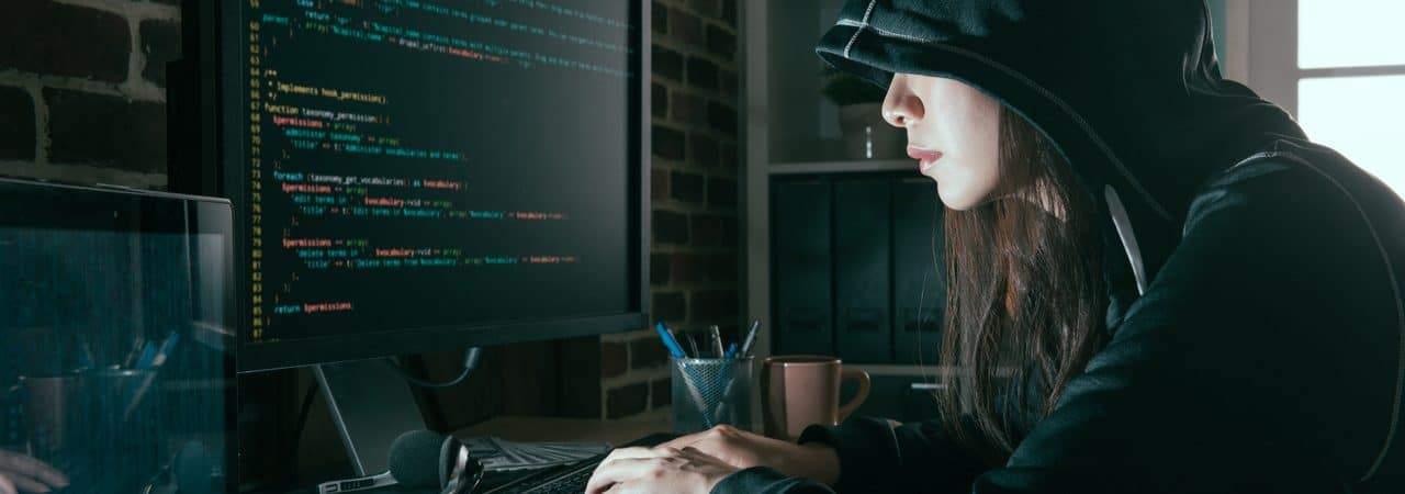 Imagem mostra uma mulher encapuzada, à frente de um computador, simbolizando um hacker
