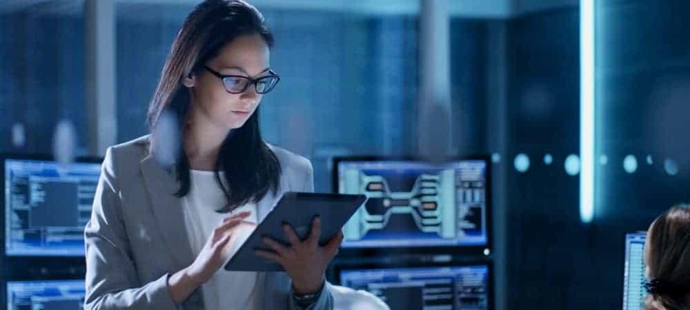 Imagem mostra uma mulher segurando um tablet dentro de uma sala com diversos computadores