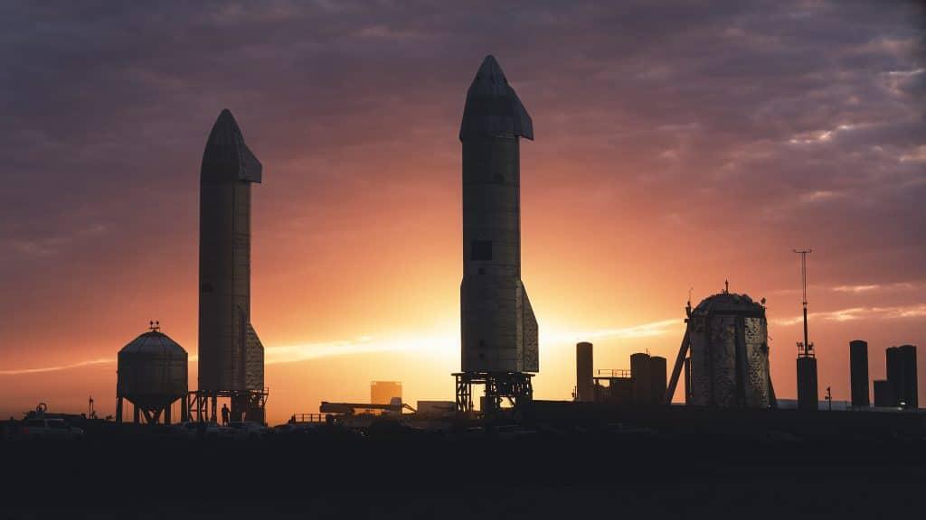 Silhueta de dois protótipos da Starship contra o pôr do sol na base da SpaceX no Texas