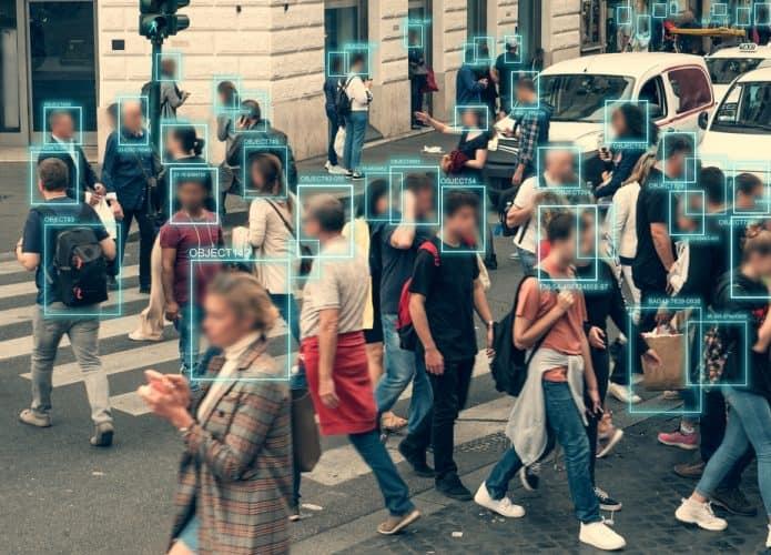 Rua cheia de pedestres, com um quadradinho verde em cima de cada rosto, indicando que há uma tecnologia de reconhecimento facial atuando no cenário