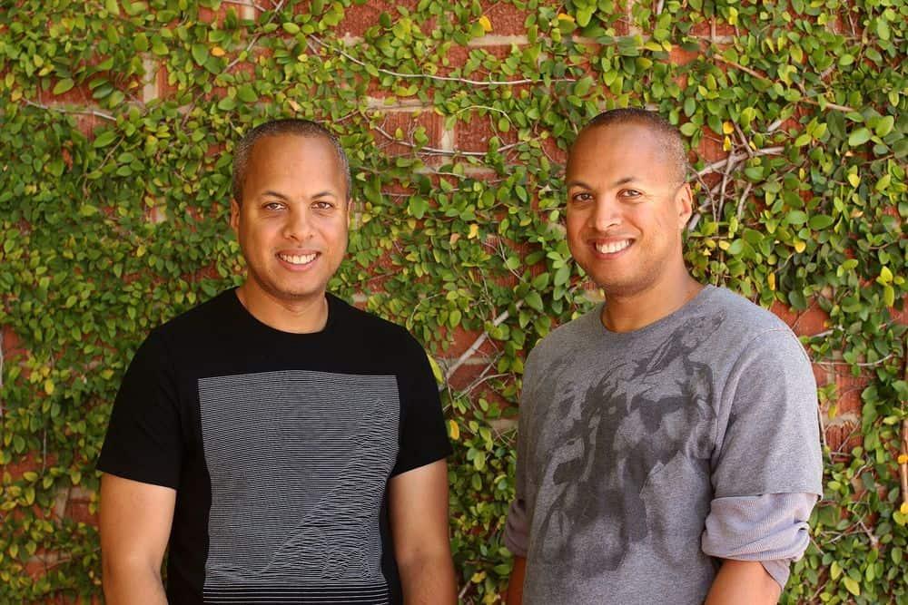 Imagem mostra os irmãos gêmeos Tom e Tony Cannon. Tom veste uma camiseta preta, de manga curta, enquanto Tony está com um blusão cinza e mangas dobradas. Ambos sorriem com um uma parede de tijolos e plantas ao fundo