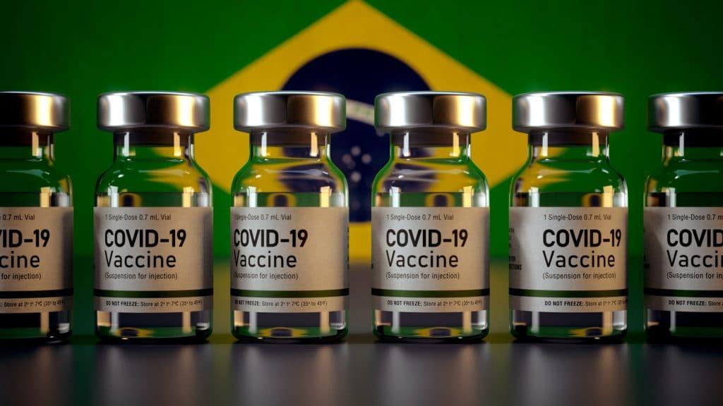 ampolas de vacina na frente de uma bandeira do brasil
