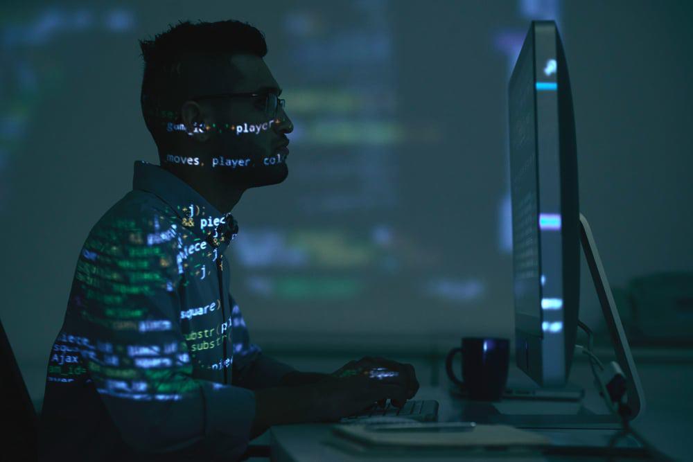 homem sentado de frente para o computador, com código de programação sendo projetados em sua frente