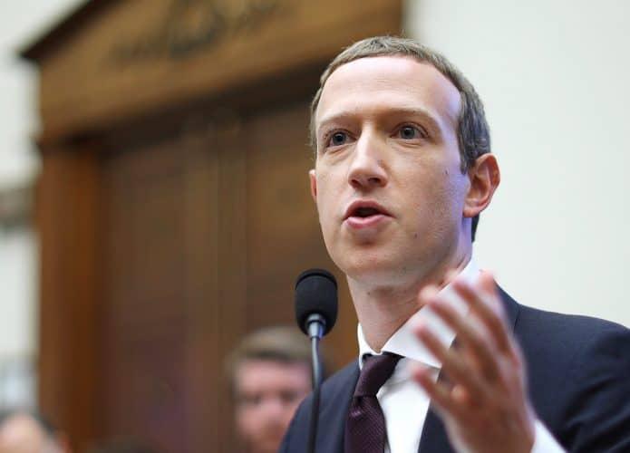 Inagem mostra o CEO do Facebook, Mark Zuckerberg, sentado em um acadeira de madeira, respondendo a perguntas durante uma audiência. Ele veste terno preto com gravata da mesma core está com o cabelo curto