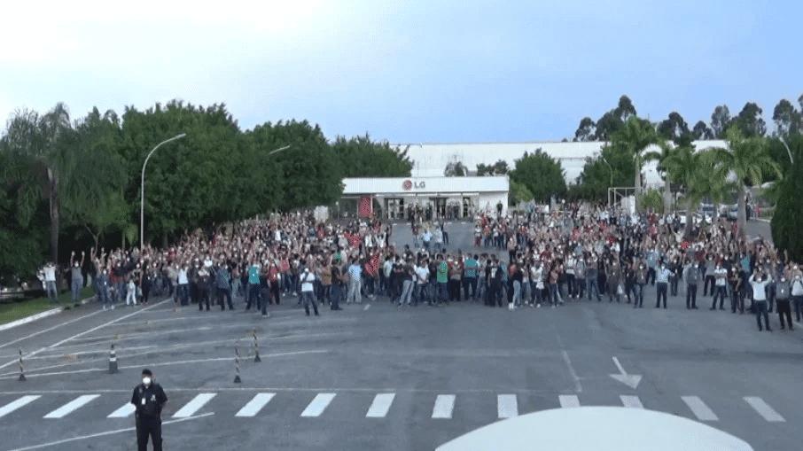 La foto muestra la fachada de la fábrica de LG en Taubaté, con varias personas manifestando frente a ellos