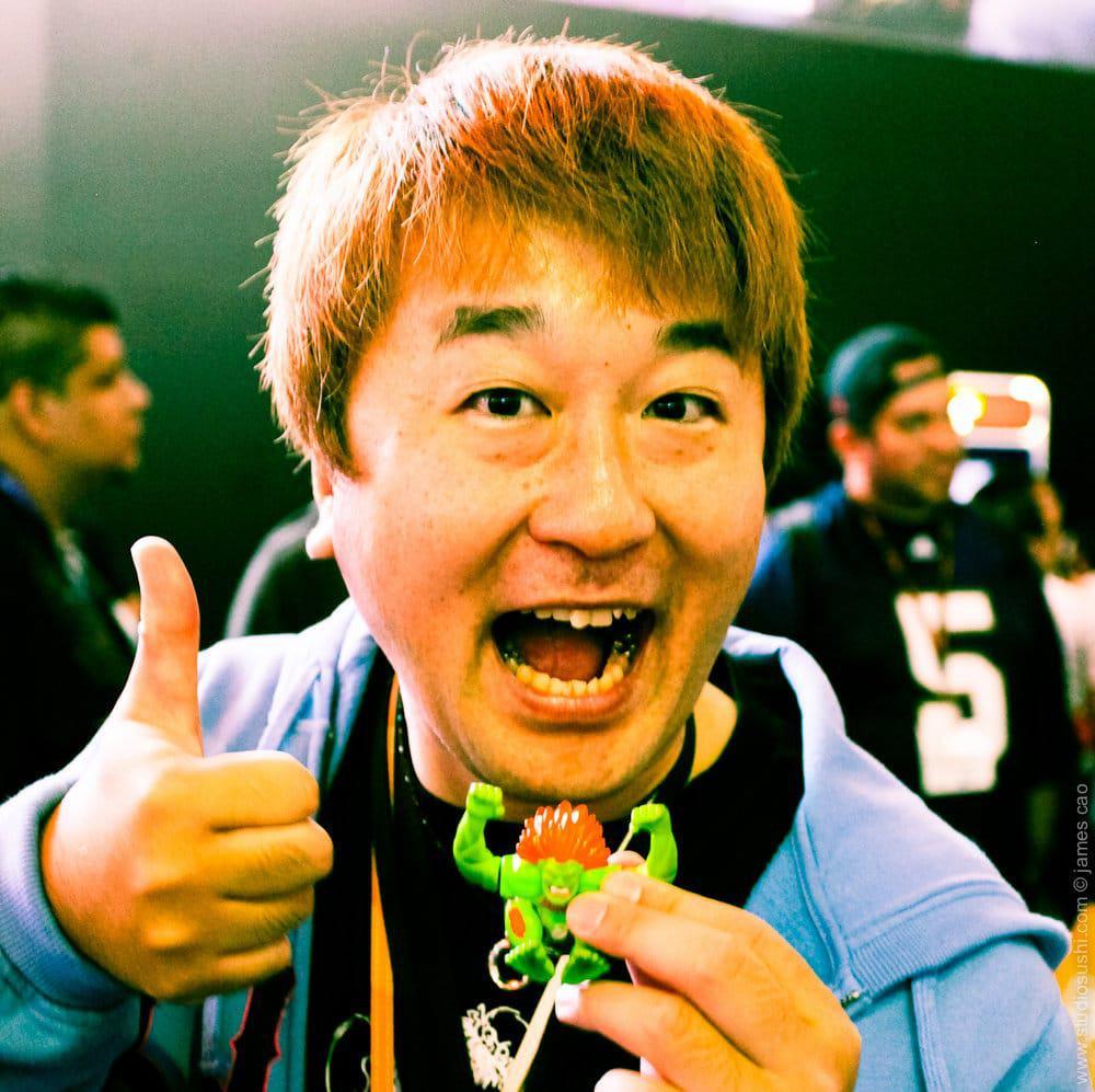 Yoshinori Ono, que deixa a Capcom depois de mais de 20 anos, é mostrado na imagem segurando um boneco do personagem Blanka, que ele carregava consigo para todos os países que visitava