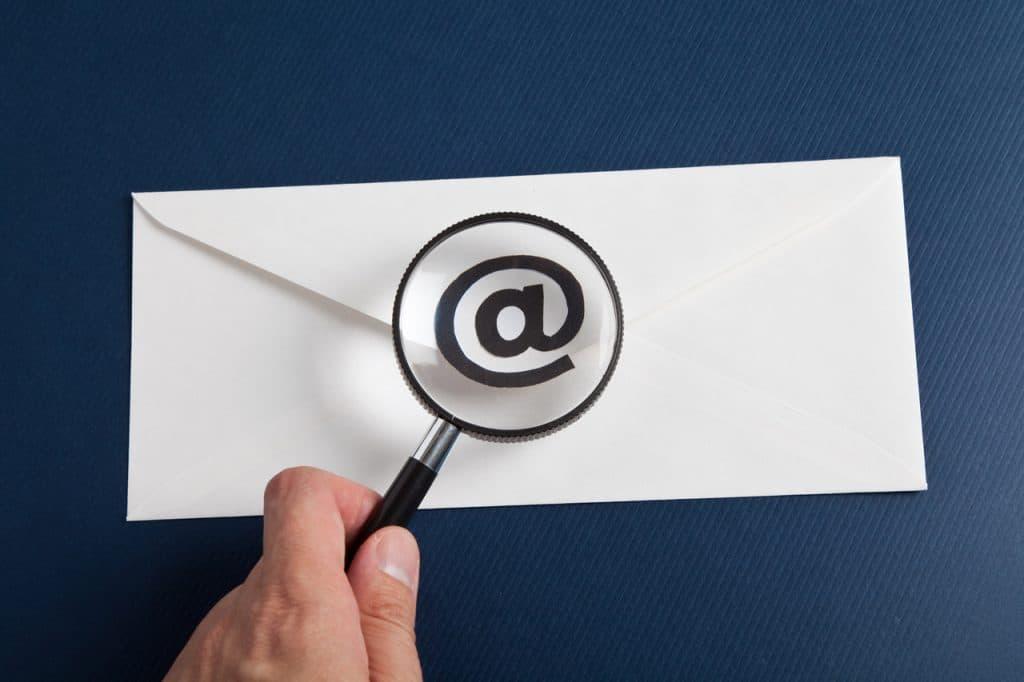 Ilustração de uma lupa em um e-mail para detectar malwares